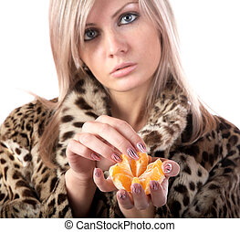 The girl in fur coat holds hand tangerine close up