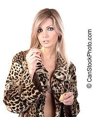 The girl in fur coat holds in hand tangerine on white...