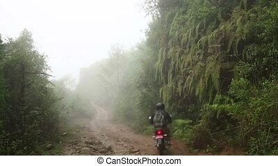 Man riding motorbike in mist, at himalayas - Man riding...