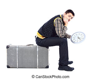 Young man waiting at airport, holding big clock, isolated...