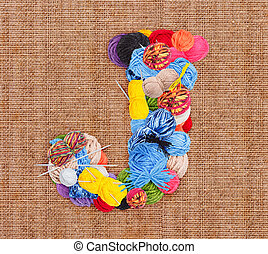 Letter J made of knitting yarn on burlap background