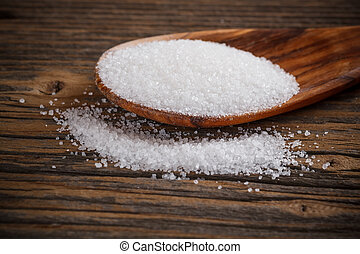 White sugar in a wooden spoon