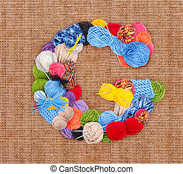 Letter G made of knitting yarn on burlap background