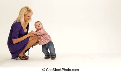 Learning to walk - Mother helping her little son to walk