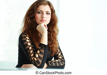 Young beautiful thoughtful woman looking at camera