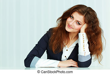 Beautiful young businesswoman sitting at the table in office