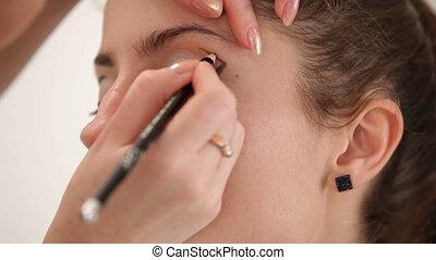 Applying eyeliner - Visagist applying black eyeliner