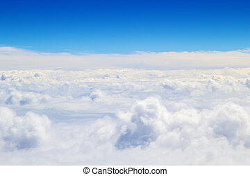 Horizontal cloudscape scenery with blue sky above.