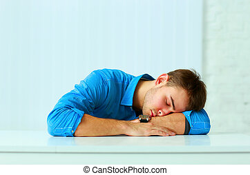 Young tired businessman sleeping at workplace in office