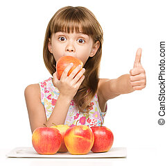 Little girl with apples is showing thumb up sign
