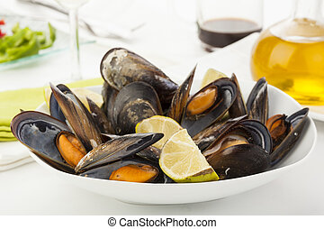 plate of coocked mussels with lemon isolated over white -...