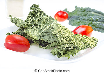 Kale chips - Dry kale leaves with tomate on white background...