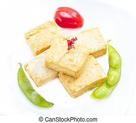 Fried tofu. - Fried tofu served with soy bean and tomato.