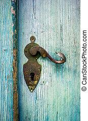 Antique Doorknob on a light blue wooden door