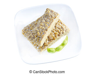 Yellow tempeh. - Yellow tempeh served on plate with edamame.