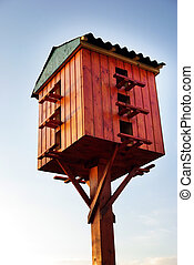 Wooden birdhouse on a wooden post in the outdoors