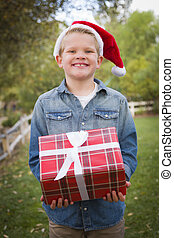 Handsome Young Boy Wearing Holiday Clothing Holding Christmas Gift Outside.