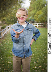 Handsome Young Boy Tossing Up Baseball in the Park -...