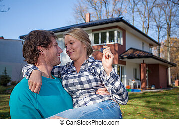 Couple moving into a new house - Young man moving into a new...