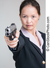 Woman aiming a hand gun - Close up portrait of woman in...