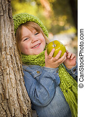 Young Girl Wearing Green Scarf and Hat Eating Apple Outside...