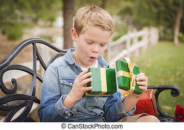 Suprised Young Boy Opens Christmas Gift Outside