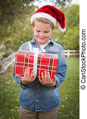 Young Boy Wearing Santa Hat Holding Christmas Gift Outside