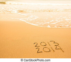 2013 - 2014 written in sand on beach texture, soft wave of the sea.