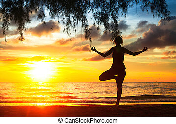 Silhouette of woman practicing yoga on the beach during a beautiful sunset