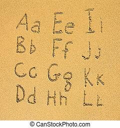 Alphabet A-L written on a sand beach