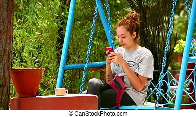 Female tourist on swing using her mobile phone
