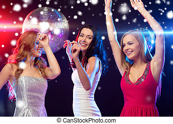 three smiling women dancing in the club - party, new year,...