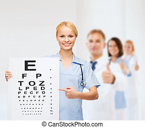 smiling female doctor or nurse with eye chart - healthcare,...