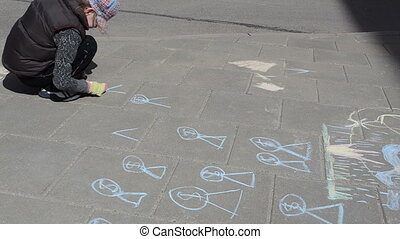 yard draw chalk - girl with hat drawing with blue piece of...
