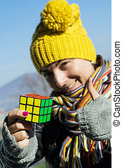 Woman enjoys for resolving of Rubiks cube - Woman with...