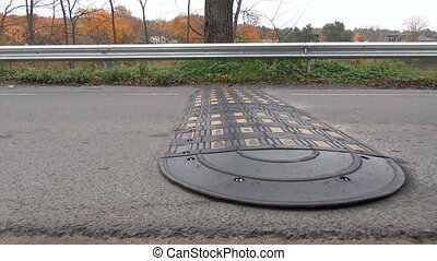 speed bump road safety - Speed bump on rural road and cars...