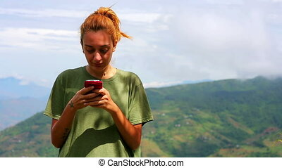 Female tourist text messaging on top of mountain at...