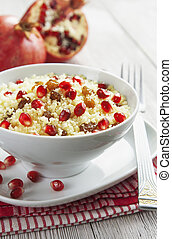 Couscous with pomegranate, raisins and spices in white bowl...