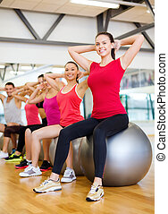 group of people working out in pilates class - fitness,...