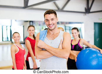 smiling man standing in front of the group in gym - fitness,...
