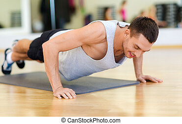 smiling man doing push-ups in the gym - fitness, sport,...