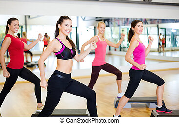 group of smiling people doing aerobics - fitness, sport,...