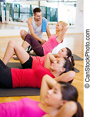 group of smiling women doing sit ups in the gym - fitness,...