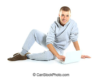 Handsome guy working on a laptop and sitting on the floor,...