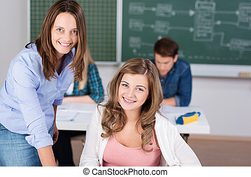 Smiling student in class with her teacher
