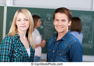 Smiling teenage couple in the classroom - Smiling beautiful...