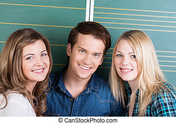 Smiling happy teenage boy and girls posing close together in...