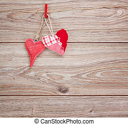 two hanging hearts - two red hearts hanging on rope on...