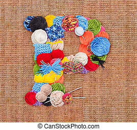 Letter P made of knitting yarn on burlap background