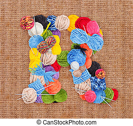 Letter R made of knitting yarn on burlap background